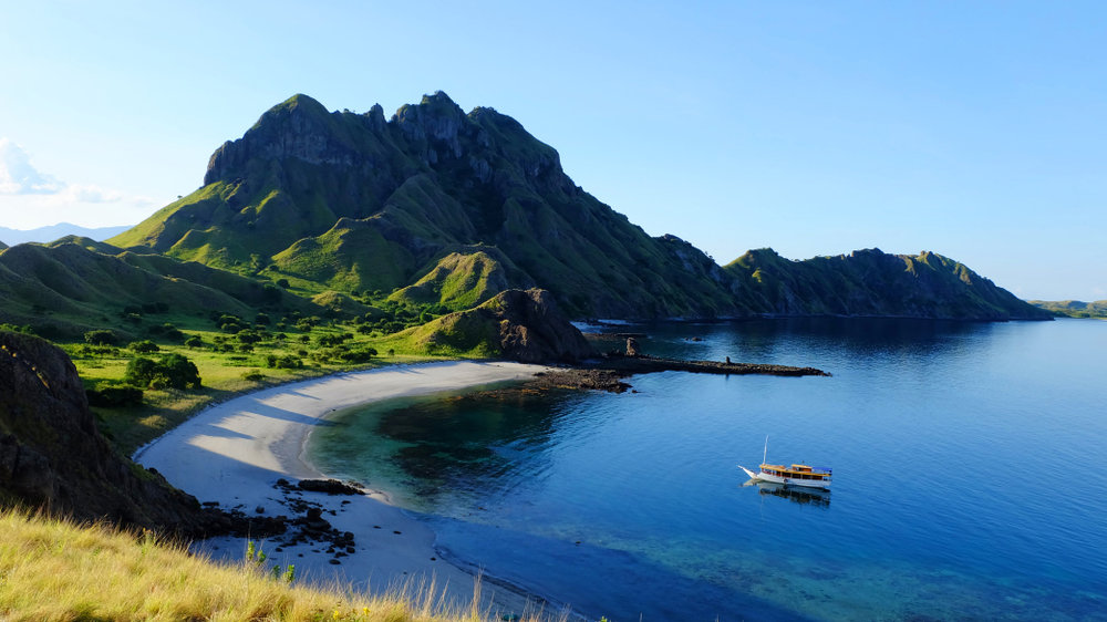 A boat approaching Padar island beach on a sunny day