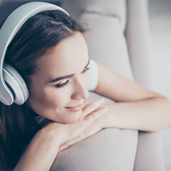 A woman is listening to a music with headphones