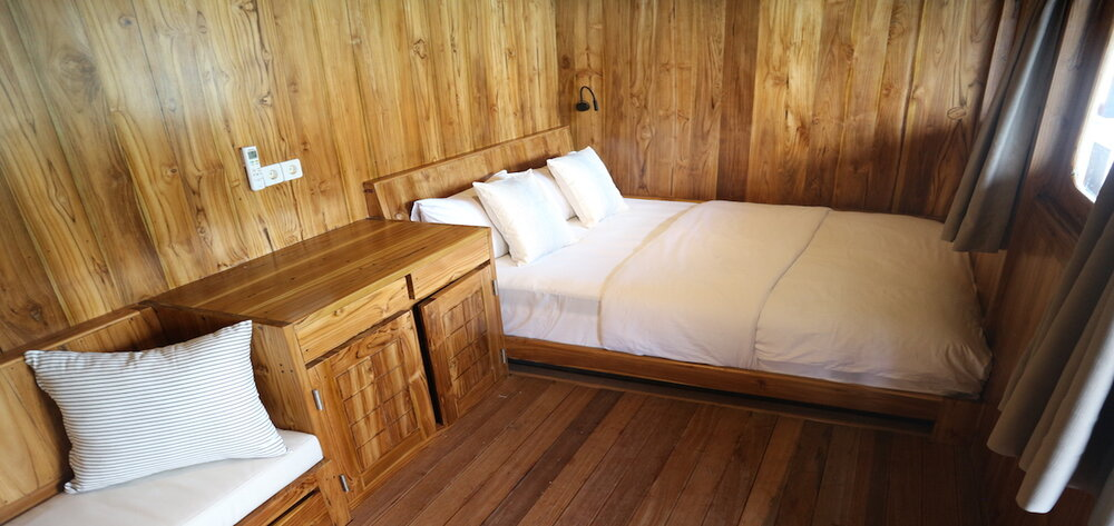 A bed with drawers inside Andamari liveaboard cabin | Hello Flores