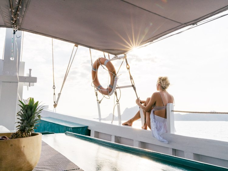 A female guest is relaxing on the starboard side of Royal Fortuna liveaboard while enjoying the view