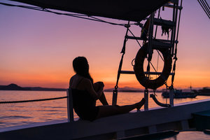 A guest is chilling on the port side of Royal Fortuna liveaboard while enjoying the sunset