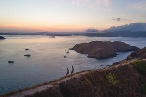 Two guests trekking on an island catching the sunset
