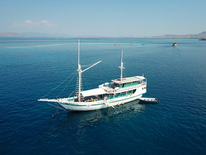 The majestic Royal Fortuna liveaboard in the middle of the blue ocean sailing away from an island