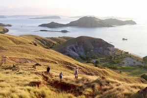 Several guests can be seen trekking in Padar with Royal Fortuna liveaboard in the background