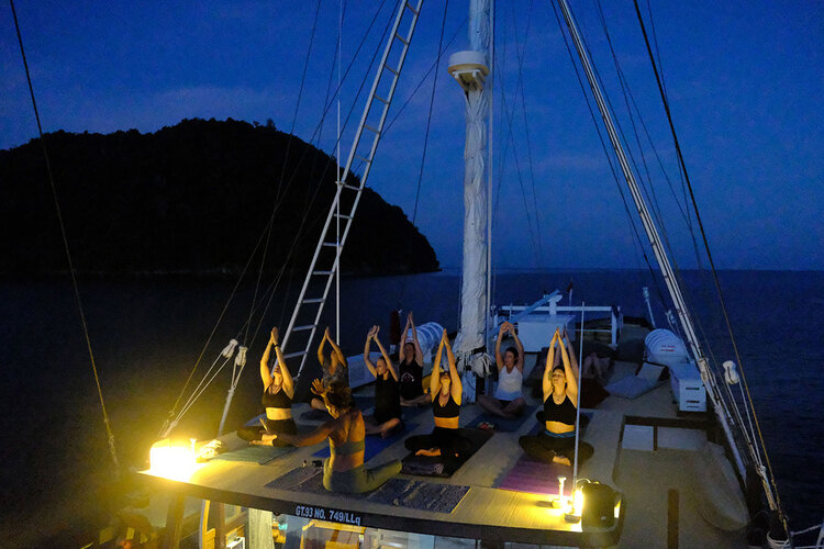 A group of women doing yoga on nighttime aboard Jakare's deck