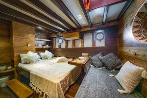 The main bedroom in Jakare liveaboard provides a queen size bed, couch, cupboard and wall decorations