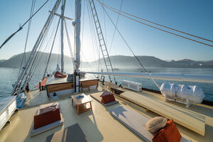 The front side of deck in Jakare liveaboard offers plenty of comfy mats and tables for relaxing