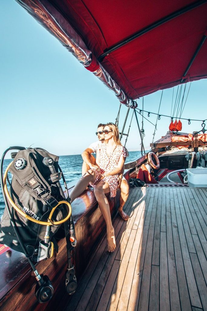 A couple is sitting on the Manta Mae liveaboard port side