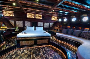 A nice cabin with a big double bed and a comfortable couch inside Manta Mae liveaboard