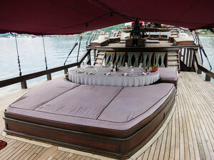 Relax on a couch in the deck of Manta Mae liveaboard covered by a roof