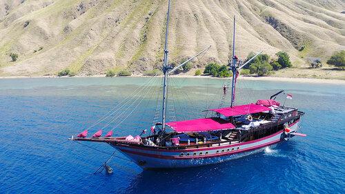 Manta Mae liveaboard with its sail down near an island