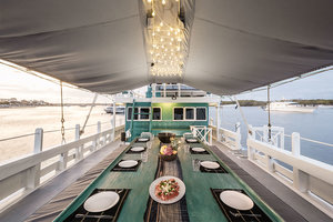 A large dining table fit for many people is provided by Royal Fortuna liveaboard on the deck