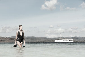 A guest walking in the beach with the Splendour liveaboard in the background