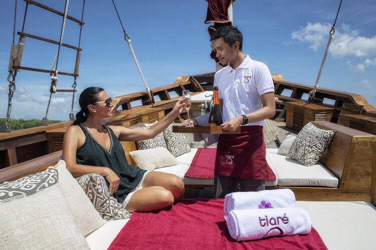 Tiare liveaboard crew serve a drink to the guest | Hello Flores