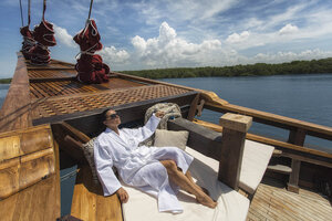 A guest sitting in Tiare liveaboard deck while enjoying the view
