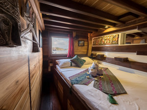 The bedroom in Wisesa liveaboard provides a wall decorations and a huge window