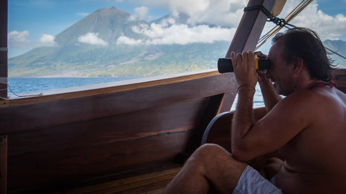 A guest observe the landscape by looking through a binocular in Wisesa liveaboard
