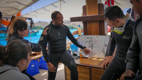 Diving instructors briefing the guests in Wisesa liveaboard before diving