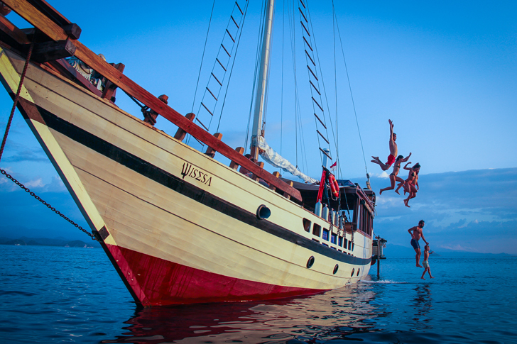 Several guests are jumping from the Wisesa liveaboard to swim in the sea