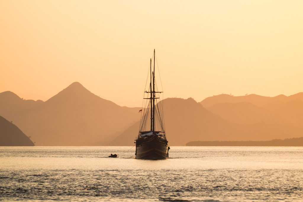 A boat is sailing in the evening